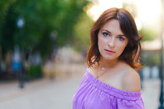 Retrato al aire libre Mujer hermosa joven que visita el centro de ciudad en un día soleado, en un vestido púrpura con la calle en Fotos de archivo