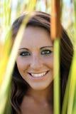 Retrato al aire libre sonriente de la muchacha adolescente en medio de cattails Imagen de archivo libre de regalías