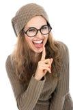 Retrato alegre da jovem mulher que mantém o dedo em seus bordos e Imagens de Stock Royalty Free