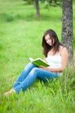 Retrato ao ar livre de uma leitura bonito adolescente Fotos de Stock