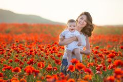 Retrato ao ar livre A mãe nova e sua filha apreciam o tempo da vida junto em um campo da papoila Conceito do amor e da família fe imagens de stock royalty free