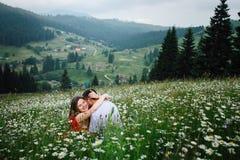 Retrato ao ar livre romântico A mulher de sorriso loura lindo está abraçando felizmente seu noivo ao sentar-se no chamonile Fotos de Stock