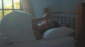 Retrato apenas da jovem mulher acordada que encontra-se na cama em casa na manhã vídeos de arquivo