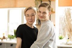 Retrato ascendente cercano de dos hombres gay internacionales jovenes en la ropa casual, hombres rubios asiáticos uno en las len imagen de archivo libre de regalías