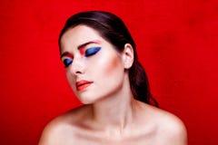 Retrato ascendente cercano de la belleza de la mujer con maquillaje colorido en backround rojo Imágenes de archivo libres de regalías