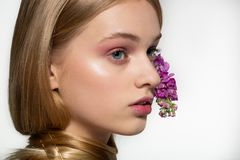 Retrato ascendente cercano de la chica joven con los ojos azules, maquillaje brillante, cuello envuelto en el pelo, flores p?rpur imagen de archivo libre de regalías