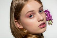 Retrato ascendente cercano de la chica joven con los ojos azules, maquillaje brillante, cuello envuelto en el pelo, flores p?rpur imágenes de archivo libres de regalías