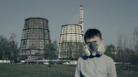 Retrato ascendente cercano de la máscara de la contaminación del muchacho que lleva joven contra las chimeneas de la fábrica Conc almacen de metraje de vídeo