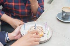 Retrato ascendente cercano de la mano de la luz de la vela para arriba en crepe a preparar la fiesta de cumplea?os de la sorpresa imágenes de archivo libres de regalías