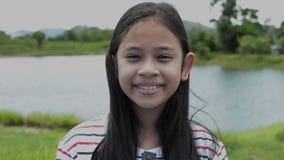 Retrato ascendente cercano de la muchacha asiática preciosa que sonríe en el campo metrajes