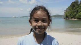 Retrato ascendente cercano de la muchacha linda que sonríe en la playa almacen de video