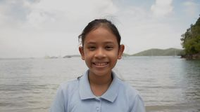 Retrato ascendente cercano de la muchacha linda que sonr?e en la playa almacen de metraje de vídeo