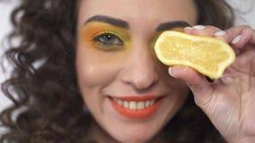 Retrato ascendente cercano de la muchacha rizada joven juguetona que sonríe y que cubre el ojo con el pedazo redondo de limón mad almacen de metraje de vídeo