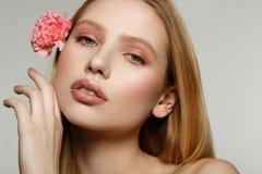 Retrato ascendente cercano de la muchacha rubia soñadora con el maquillaje de moda que toca su cara imagen de archivo libre de regalías