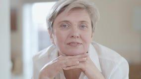 Retrato ascendente cercano de la mujer adulta que mira in camera con sonrisa agradable dentro Se empaña el fondo metrajes