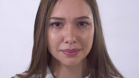 Retrato ascendente cercano de la mujer gritadora joven con los rasgones Tiroteo en el estudio en un fondo blanco almacen de metraje de vídeo