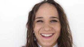 Retrato ascendente cercano de la mujer joven de la belleza con los ojos marrones, sonriendo mirando la c?mara en un fondo blanco  metrajes