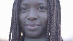 Retrato ascendente cercano de la mujer sonriente negra joven afroamericana confiada en el fondo del cielo y de la calle metrajes