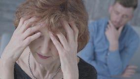 Retrato ascendente cercano de la mujer triste elegante madura mayor que lleva a cabo su cabeza en el primero plano Figura borrosa almacen de metraje de vídeo