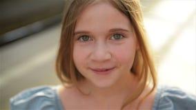 Retrato ascendente cercano de la niña hermosa con el pelo largo ligero y los ojos verdes grandes que miran in camera con relajado almacen de video