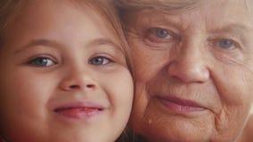 Retrato ascendente cercano de la pequeña nieta preciosa linda y de su abuelita buena agradable encantadora fotos de archivo
