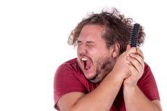 Retrato ascendente cercano de los intentos gordos del hombre para peinarse el pelo enredado y travieso con un pequeño peine negro imagen de archivo libre de regalías