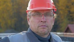 Retrato ascendente cercano de los vidrios caucásicos de In Helmet And del constructor que miran la cámara metrajes