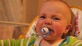 Retrato ascendente cercano de poco bebé carismático con el soother en la boca que se sienta en silla, mirando la cámara y metrajes