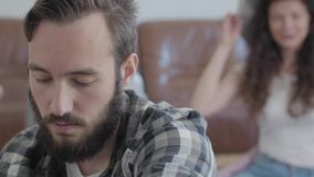 Retrato ascendente cercano de un hombre barbudo ofendido que se sienta en el primero plano mientras que su esposa feliz que inten almacen de video