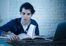 Retrato ascendente cercano de un hombre joven con exceso de trabajo y cansado que estudia tarde en la noche en luz cambiante imagen de archivo