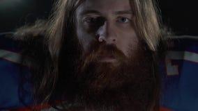 Retrato ascendente cercano de un jugador de fútbol americano barbudo con el pelo largo en el equipo de deportes que mira in camer metrajes