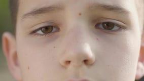 Retrato ascendente cercano de un niño pequeño que mira en la cámara metrajes