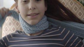 Retrato ascendente cercano de una muchacha alegre que rasga de una bufanda del cuello La muchacha recuperada y feliz Concepto de  almacen de video