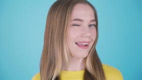 Retrato ascendente cercano de una muchacha bonita alegre con el pelo rubio largo que mira la cámara y del guiño aislado sobre azu almacen de metraje de vídeo