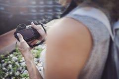 Retrato ascendente cercano de una muchacha bonita sonriente en la ropa informal que toma la foto en una cámara retra sobre fondo  fotos de archivo