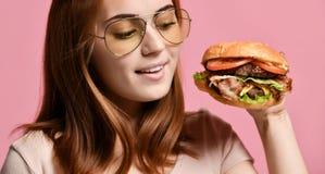 Retrato ascendente cercano de una mujer joven hambrienta que come la hamburguesa aislada sobre fondo rosado imagen de archivo