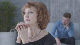 Retrato ascendente cercano de una mujer madura mayor que mira en la cámara en el primero plano La figura borrosa del triste almacen de video