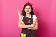 Retrato ascendente cercano del ama de casa pensativa con el delantal marrón, banda roja del pelo, camiseta blanca Soportes femeni imagen de archivo