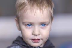 Retrato ascendente cercano del bebé caucásico lindo con la expresión muy seria de la cara Ojos azules brillantes, pelo justo Emoc fotos de archivo libres de regalías