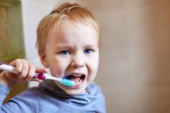 Retrato ascendente cercano del bebé caucásico lindo con la expresión muy seria de la cara que intenta limpiar los dientes con el  fotos de archivo libres de regalías