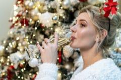 Retrato ascendente cercano del champán de consumición de la muchacha rubia hermosa joven fotos de archivo