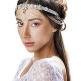 Retrato ascendente cercano del encanto de una mujer joven en un fondo blanco Foto de archivo