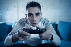 Retrato ascendente cercano del hombre adicto joven que juega al videojuego en la noche en concepto del juego y del apego imagen de archivo libre de regalías