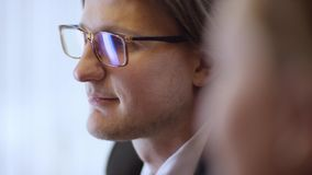Retrato ascendente cercano del hombre de negocios alegre joven con los vidrios El hombre contemporáneo confiado de risa de la sen almacen de video