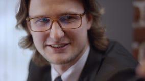Retrato ascendente cercano del hombre de negocios alegre joven con los vidrios El hombre contemporáneo confiado de risa de la sen metrajes