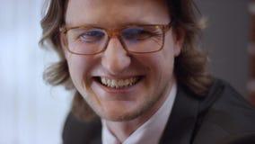 Retrato ascendente cercano del hombre de negocios alegre joven con los vidrios El hombre contemporáneo confiado de risa de la sen almacen de metraje de vídeo