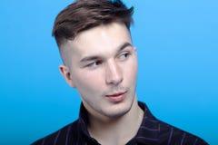 Retrato ascendente cercano del hombre hermoso joven con la mueca asombrosa en fondo azul Peinado de la moda, emociones fuertes, e imagen de archivo libre de regalías