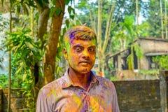 Retrato ascendente cercano del hombre indio joven con los colores de Holi en cara durante el festival de Holi en la India imagen de archivo libre de regalías