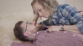 Retrato ascendente cercano del hombre y de la mujer que mienten junto en la alfombra mullida y hablar Barba del tacto de la señor metrajes
