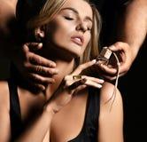 Retrato ascendente cercano del perfume auto del olor hermoso atractivo de la mujer en oscuridad foto de archivo libre de regalías